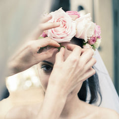 A girl getting her pink flower crown fixed on her wedding day.