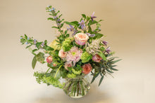 Tulip, roses, narcissus and greenery bouquet in a vase