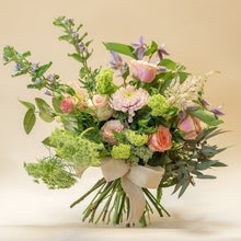 Garden style bouquet from tulips, narcissus and roses with a ribbon