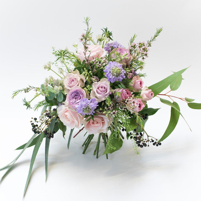Bouquet with pink and lilac roses combined with seasonal foliage