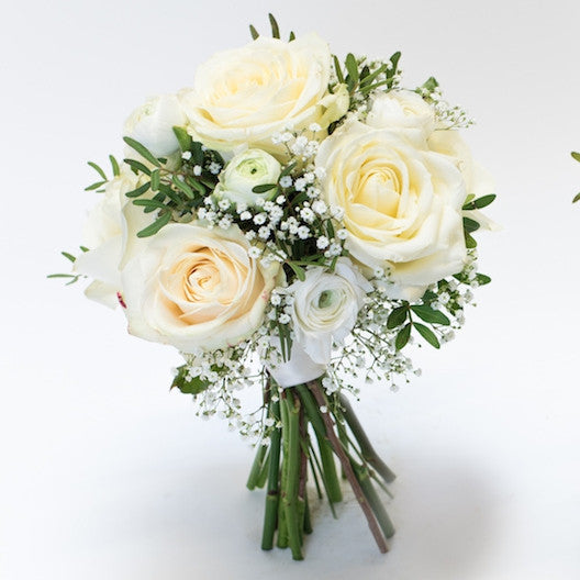 Bridesmaid bouquet of white roses and greenery in a white background