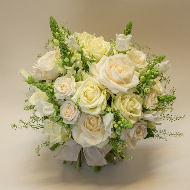 White roses bridal bouquet with greenery in a cream background