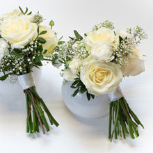 Two bridesmaid bouquets from white rouses and greenery in a white background