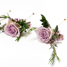 Two button holes made of violet roses and greenery