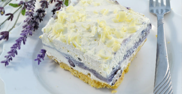 A colorful slice of Blueberry Lasagna with a graham cracker crust, blueberry middle and whipped topping with a fork to the right and some lavender laying to the left of the slice of dessert