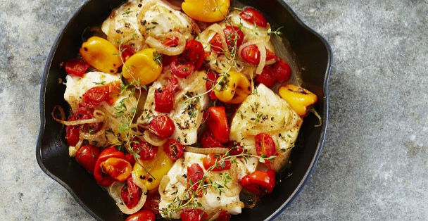 A black pan of Seared Cod with a buttery herb sauce and a mix of vegetables including sliced red and yellow peppers, tomatoes and onion on top of a granite countertop