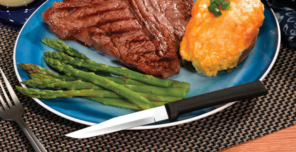 A RADA Cutlery Serrated Steak Knife with a black resin handle on a plate full of delicious asparagus, steak and cheesy potatoes