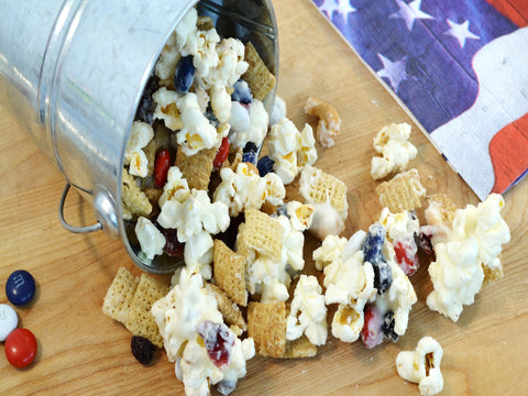 All-American Snack Mix Recipe spilling out of a metal bucket with an American flag painting to the right of the popcorn