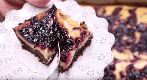 Enjoy! A Blackberry Brownie Cheesecake Bar on a white floral platter with a fork beginning to cut it in half
