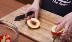 A Rada Cutlery Cook's Utility Knife slicing a peach in half on top of a wooden cutting board in front of a glass bowl of apple slices