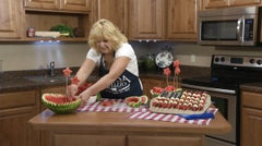 Kristi placing the wooden skewers with watermelon stars into the other watermelon bowl
