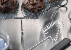 A RADA Handi-Stir next to a two chocolate muffin holder on top of a silver serving dish