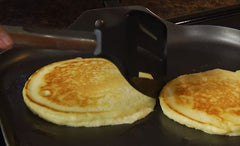 RADA Non-Scratch Spatula hovering over a couple pancakes on a griddle