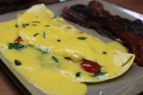 A delicious Florentine omelet with red tomatoes and several slices of maple bacon