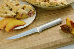 A RADA Super Parer knife next to a slice of peach pie with crisscross crust and a sliced peach to the right of the knife with a whole pie above it