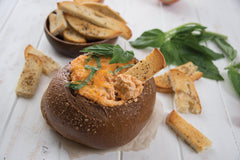 A bread bowl of RADA Cutlery's Warm Pizza Dip Quick Mix inside with a french fry scooping out some dip with another bowl of fries and green leaves to the side of the bread bowl