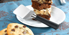 A RADA Mini Server spatula with a black resin handle next to a couple fudge bars on a white plate next to some cookies