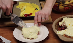 A Rada Cutlery Serrated Pie Server putting a slice of orange strawberry dessert roll onto a white plate next to another plateful of bacon and Florentine omelet