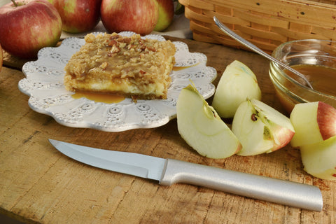 A RADA Heavy Duty Paring Knife in front of a handful of apple slices and a apple dessert bar on top of a white ceramic platter
