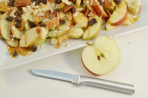 A RADA high carbon stainless steel Regular Paring Knife with a silver brushed aluminum handle next to a halved apple and some apple-crisp on a white platter