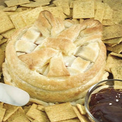 A cheese pastry wheel with a toasted crust topping surrounded by wheat crackers and a small glass bowl of raspberry sauce