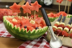 Finished watermelon bowl decorated with slices of bananas, blueberries, cubes of watermelon and star skewers next to some fruit kabobs and a RADA Ice Cream Scoop leaning up against it