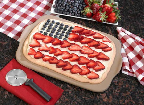 An American flag colored fruit pizza with sliced red strawberries and blueberries next to a RADA Cutlery Pizza Cutter and a couple handkerchiefs