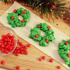 Christmas wreath cookies with red hot candies in green frosting on a strip of opaque parchment paper
