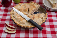 A RADA Slicer knife with a black resin handle with a black resin handle on top of a apple pie with a few apple slices beside the pie over a red checkered table cloth