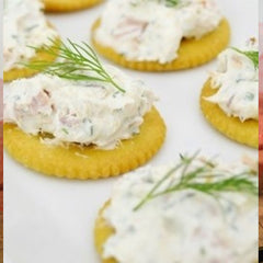 Circular butter crackers with Smoked Salmon Spread on top of each cracker with a small sprig of garnish