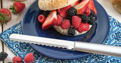 A RADA Bagel Knife with a silver brushed aluminum handle next to a bagel stuffed with raspberries, blackberries and sliced strawberries on top of a purple plate over a blue placemat