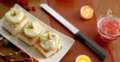 A RADA Cutlery six inch bread knife with a black handle next to three dessert bars with white frosting on a white platter next to some orange slices