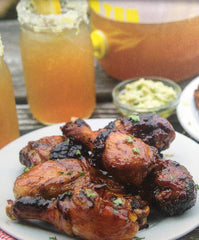 BBQ'd drumsticks in front of a mason jar of sweet tea and party dip