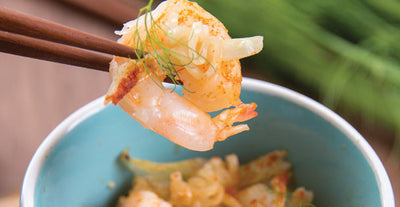 Skewered shrimp hovering above a cup