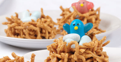 An Easter treat creation with a candy blue bird rising from its nest of candy eggs
