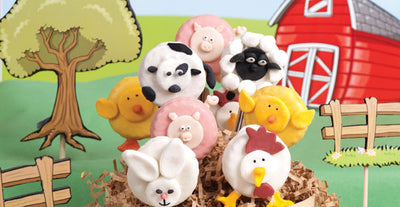 A farmhouse treat including a candy cow, chicken, pig, duck and bunny on paper mache hay