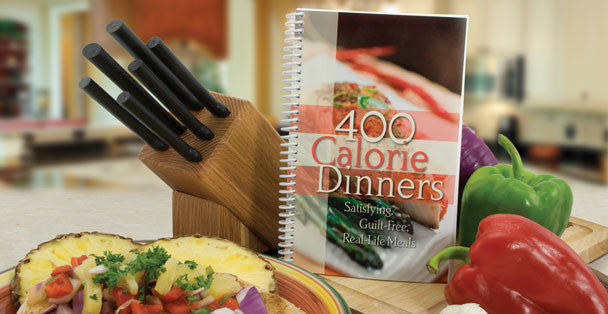 400 Calorie Dinners cookbook next to a Rada wooden knife block and fresh vegetables