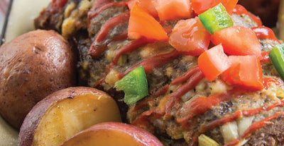 Meatloaf with cubed tomatoes and green peppers on top beside some sliced potatoes
