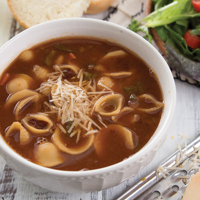 Pasta Fagioli Soup with a shredded Swiss Cheese topping beside a garden salad and bread slices