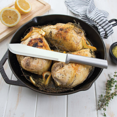 Silver Butcher Knife setting on top of chicken in cast iron skillet