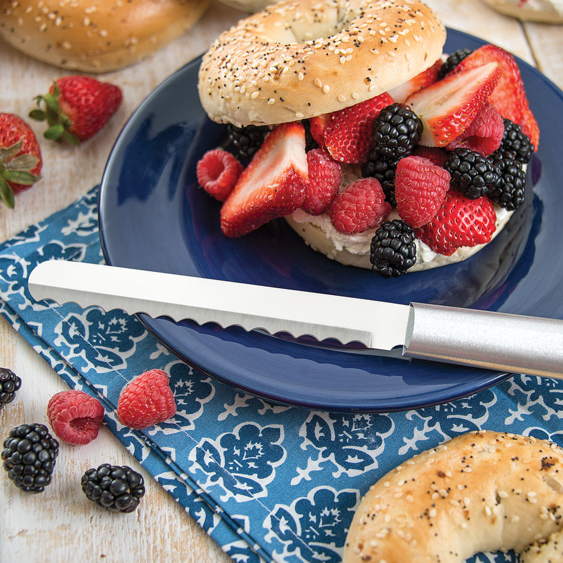 Bagel Knife in front of a fruit-filled bagel
