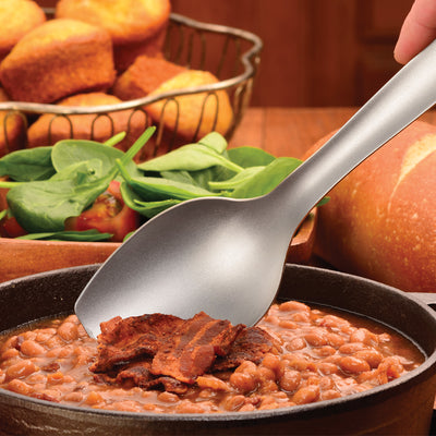 Cook's Spoon scooping a portion of baked beans with a bacon topping