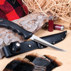 Sportsman Knife with leather scabbard next to a piece of wood
