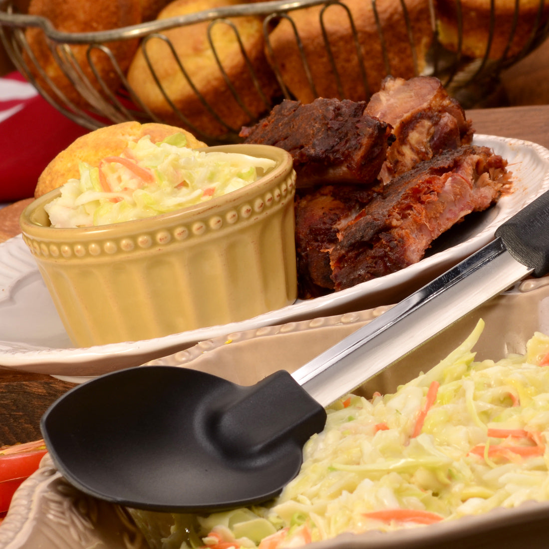 Non-Scratch Spoon next to a dish of coleslaw and ribs