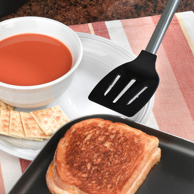 Non-Scratch Spatula flipping a grilled cheese sandwich over with a bowl of tomato soup nearby