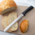 "Rada Cutlery Anthem Wave 8"" Bread knife with sliced bread loaf."