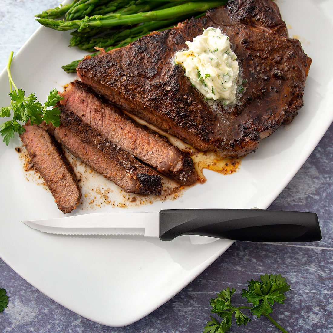 Rada Cutlery Anthem Wave Serrated Steak knife on plate with sliced steak.