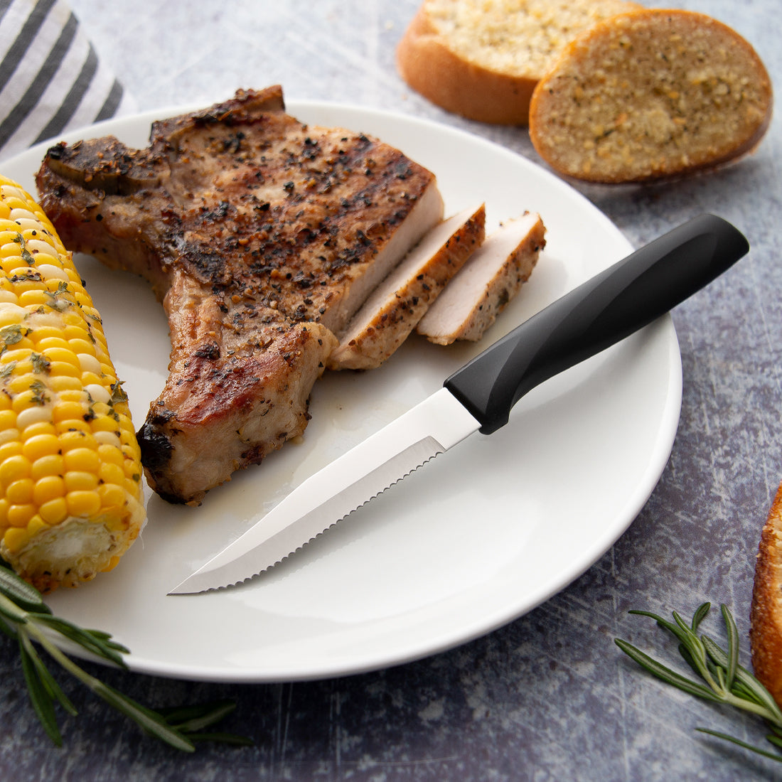 Rada Cutlery Anthem Wave Serrated Steak knife on white plate with sliced steak