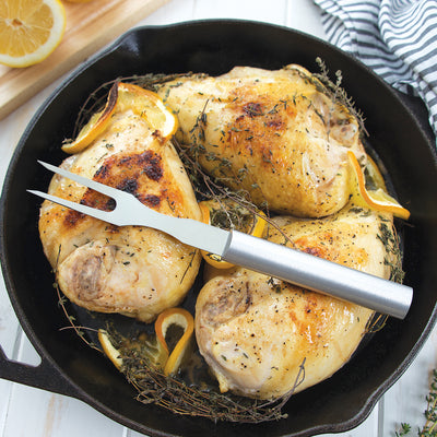 Rada Cutlery Carving Fork with silver handle on chicken in cast iron pan.