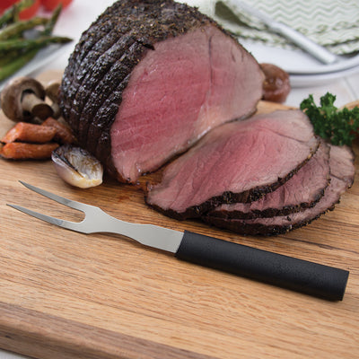 Carving Fork knife with black handle on cutting board with sliced meat.